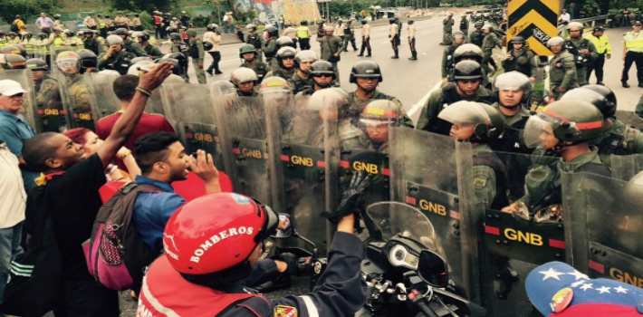 The Venezuela National Guard use anti-riot gear to prevent the passage of opposition activists demanding a Venezuelan recall referendum on Nicolás Maduro